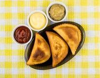 Chebureks fritados no prato e bacias com molhos diferentes Imagem de Stock