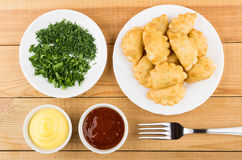 Chebureks in plate, sauces in bowl, chopped greens in saucer Stock Images