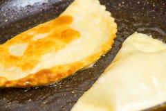 Chebureks wordt geroosterd op hete koekepan blozende knapperige smakelijk royalty-vrije stock foto's