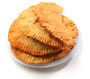 Chebureky. Stuffed yellow Chebureky on the plate over white background Stock Images