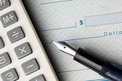 Check. Calculator and  fountain pen on a blank check Royalty Free Stock Image