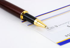 Closeup of pen on check. Closeup of ballpoint pen resting on unsigned bank check, white background stock photo