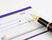 Closeup of blank check and pen. Closeup of ballpoint pen and blank check on white background royalty free stock photography