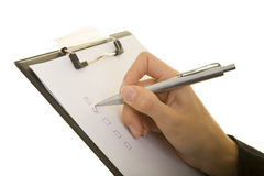 Check applicable. Hand with pen ticks check boxes on a clipboard royalty free stock photos