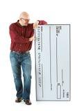 Check: Bald Man Looks At Novelty Sized Check Royalty Free Stock Photo