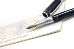 Check book and pen. Closeup of open check or cheque book and fountain pen, isolated on white background Stock Image