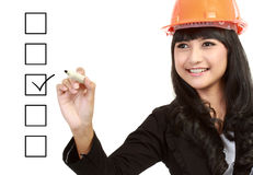 Check box. Female engineer with a pen marking on check boxes Royalty Free Stock Images