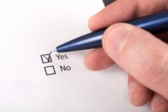 Check boxes with yes and no question, hand with pen check yes Stock Images