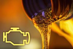 Check engine lamp and liquid stream of motorcycle motor oil flows from the neck of the bottle close-up. stock images