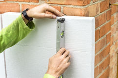 Check flatness of the wall using a level. Check the evenness of the walls using foam plastic level Stock Photo