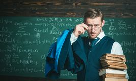 Check homework. Teacher formal wear and glasses looks smart, chalkboard background. Teacher finished explanation. Chalkboard full of math formulas. Man in end royalty free stock images