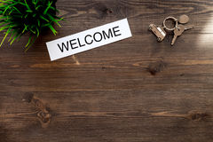 Check in at the hotel. Word welcome near room keys on dark wooden table background top view copyspace Stock Photos