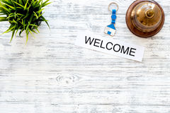 Check in at the hotel. Word welcome near service bell on light wooden table background top view copyspace. Check in at the hotel. Word welcome near service bell Royalty Free Stock Photography