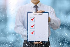 Check list in the hands of a businessman in network . royalty free stock photography