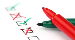 Check list with two pens. On white paper Stock Photography