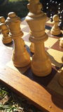 Check. A low angle shot of several chess pieces backlit by sunlight on a wooden chessboard Stock Photo