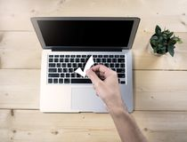 Check mark sign holding by hand holding with notebook. Check mark sign holding by hand holding with empty computer notebook screen, wood table, top view Royalty Free Stock Photo