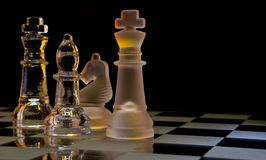 Check Mate. Chess Pieces on a glass chessboard Royalty Free Stock Image