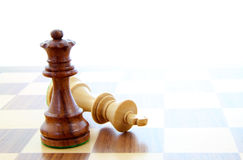 Check mate. Two wooden chess pieces alone on a chess board Royalty Free Stock Photos