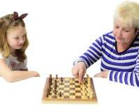 Check-mate! Grandma wins! Grandmother and granddaughter play che stock photo