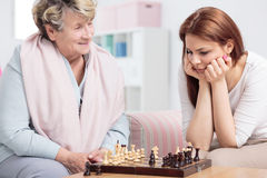 Check-mate! Grandma wins!. Grandmother playing chess with her granddaughter sitting in cozy interior Stock Images