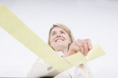 Check off the list. Woman placing reminder notes in check shape on transparent surface Royalty Free Stock Photo
