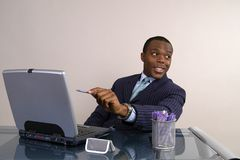 Check this out. A businessman points to something on his computer screen Royalty Free Stock Photos