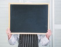 Check out cooking tips. Chef hold blackboard copy space hide face behind. Recipe concept. Cooking delicious meal step by. Step. Menu for today. List ingredients royalty free stock photo
