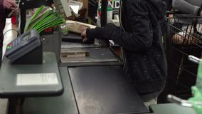 Check-out at a grocery store (3 of 9). An associate checks out and bags groceries stock footage