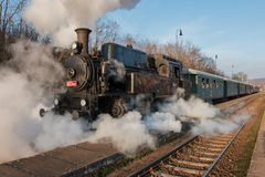Check out the historic steam train on tracks. Historic Steam Train at railway station Royalty Free Stock Images