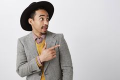 Check this out, man. Portrait of handsome intrigued dark-skinned male in stylish hat and classy suit, pointing and. Looking right with interest, wanting to come Stock Photo