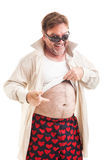 Check Out My Abs. Humorous photo of a scruffy middle aged man lifting his shirt and pointing to his overweight stomach.  Isolated on white Royalty Free Stock Image