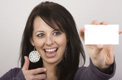 Check Out My Card. A beautiful woman points at her blank card. Sharp focus on her face Royalty Free Stock Photo