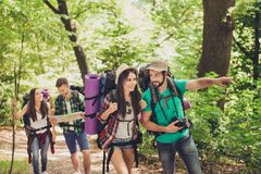 Check it out! Young excited tourists are walking in the spring canyon, having all needed for camping, talking, relaxing. Handsome men attractive ladies Royalty Free Stock Images