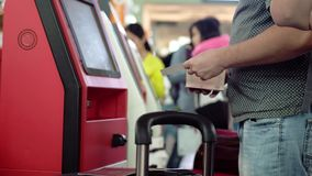 Check-in at self help desk in the airport, close up of hands with passport on a suitcase on a foreground. 3840x2160. Check-in at self help desk in the airport stock footage