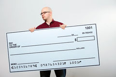 Check: Serious Man With Check Glances to Side. On white background series of a Caucasian man with an oversized bank check Royalty Free Stock Images