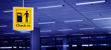 Check-in sign at airport. Yellow check-in sign at airport. Copy-space stock photos