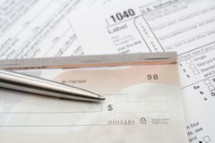 Check and silver pen with tax forms Stock Image