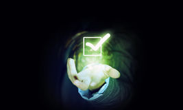 Check tick icon. Close up of businessman's hand holding check mark icon in palm stock image