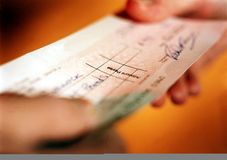 Check transacation. Person handing over check in financial transaction Stock Photos
