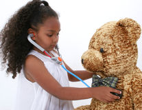 Check Up. Adorable young girl giving large bear a health check up with toy stethoscope. Shot in studio over white Stock Photos