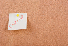 Check-up. Ckeck-up post-it note pinned to corkboard Royalty Free Stock Image