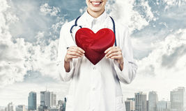 Check your heart. Close view of woman doctor against city background holding red heart stock image