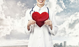 Check your heart. Close view of woman doctor against city background holding red heart stock photography