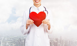 Check your heart. Close view of woman doctor against city background holding red heart royalty free stock photos