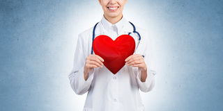 Check your heart. Young woman doctor against blue background holding red heart stock photos