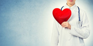 Check your heart. Young woman doctor against blue background holding red heart stock images