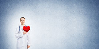 Check your heart. Young woman doctor against blue background holding red heart stock photography
