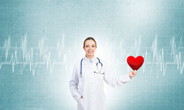 Check your heart. Young woman doctor against blue background holding red heart royalty free stock images