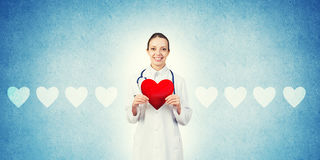 Check your heart. Young woman doctor against blue background holding red heart royalty free stock photos